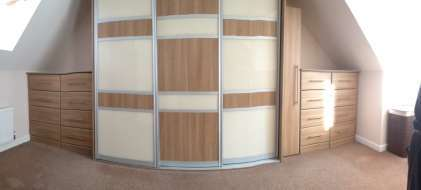 Panoramic of wardrobe between the eaves with fitted drawers at both sides
