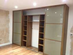 Light brown glass wardrobes doors with a walnut frame with middle doors open (from the right view)