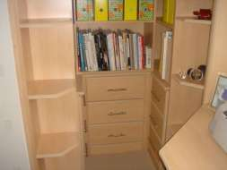 Open wing end shelves with drawers and bookcase fitted into an alcove